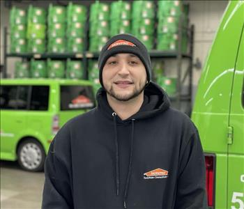 Male with hat standing in front of SERVPRO vehicles